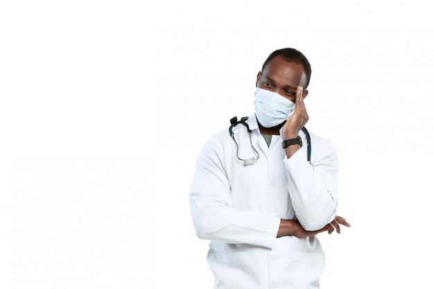 Мужской молодой доктор при стетоскоп и лицевой щиток гермошлема изолированные на белизне