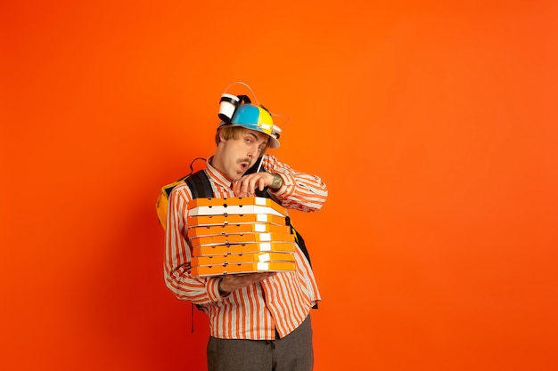 検疫中の非接触配送サービス。男は断熱中に食べ物や買い物袋を届けます。オレンジに分離された配達員の感情