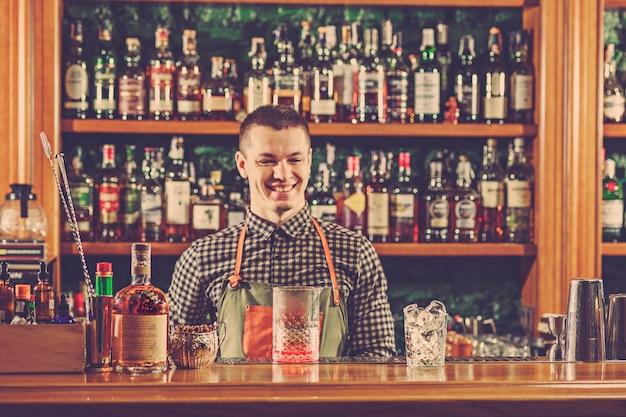 Бармен предлагает алкогольный коктейль за барной стойкой в баре