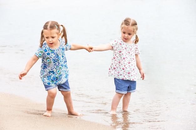 海のビーチで子供たち。海の水に沿って行く双子。