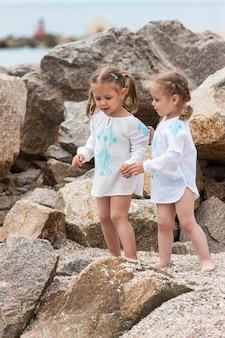 海のビーチで子供たち。双子が石と海の水に立ち向かいます。