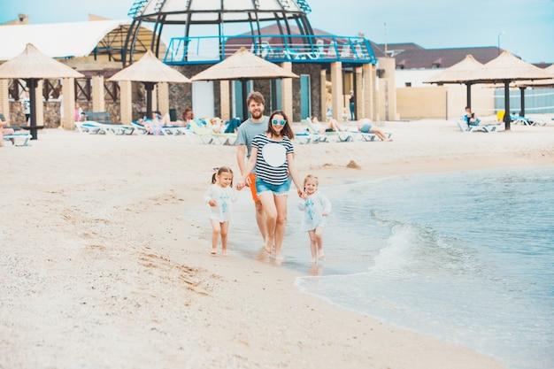 家族での休暇の両親と海の夏の日の子供