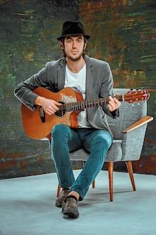 Крутой парень в шляпе играет на гитаре на сером пространстве