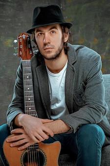 Крутой парень сидел с гитарой на сером пространстве