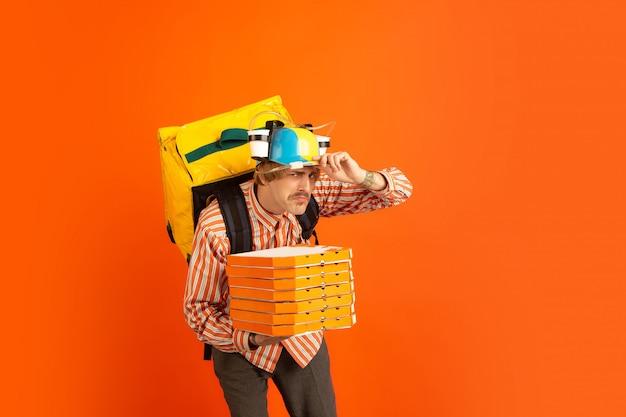 検疫中の非接触配送サービス。男は断熱中に食べ物や買い物袋を届けます。オレンジ色の背景に分離された配達員の感情。