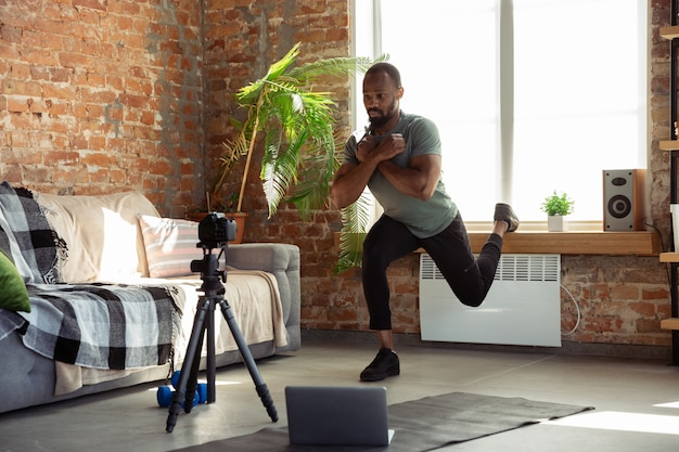 Молодой афроамериканец обучает на дому онлайн-курсы фитнеса, аэробики, спортивного образа жизни во время карантина, записи на камеру, трансляции