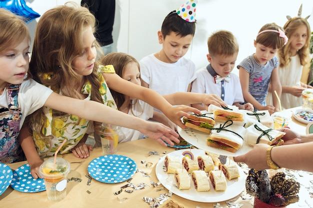 Девушка на день рождения украшения. сервировка стола с пирожными, напитками и гаджетами для вечеринок.