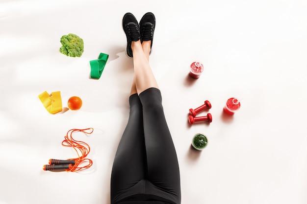 Спортивная девушка со здоровой пищей на полу