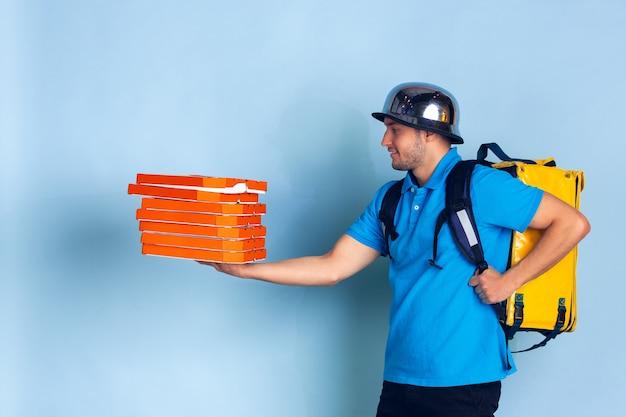 検疫中の非接触配送サービス。男は断熱中に食べ物や買い物袋を届けます。青に分離された配達員の感情