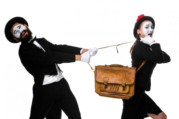 ビジネスの男性と女性のブリーフケースを争って