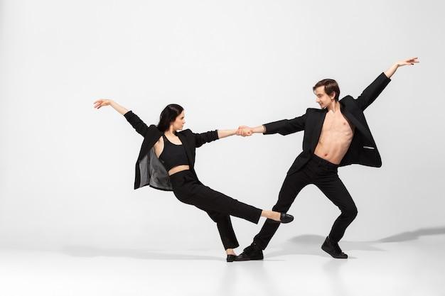 白で隔離される最小限の黒のスタイルで若くて優雅なバレエダンサー