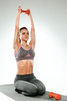 いくつかのストレッチ体操をしている美しいスリムなブルネット