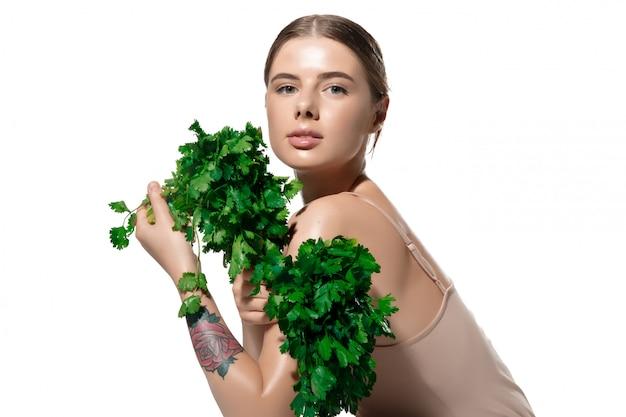 刺激を受けました。白で彼女の顔に緑の葉を持つ美しい若い女性のクローズアップ。化粧品とメイクアップ、ナチュラルでエコなトリートメント、スキンケア