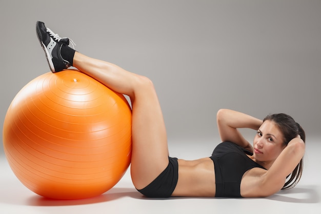 Спортивная женщина делает упражнения на фитболе