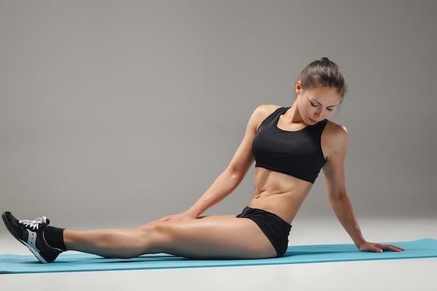 Мускулистая молодая женщина спортсмен растяжения