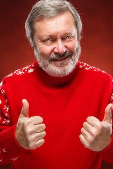 Пожилой мужчина показывает знак ок в красном рождественском свитере