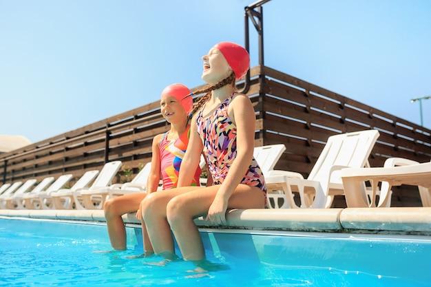Портрет счастливых улыбающихся красивых девушек-подростков у бассейна