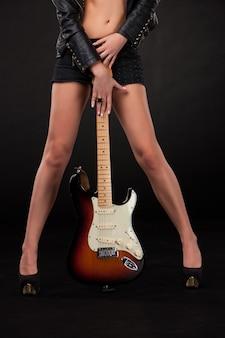 女性の脚とエレキギターで手