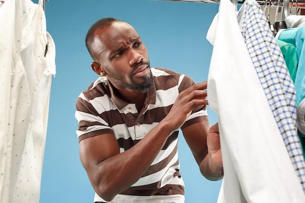 ひげの店でシャツを選択するとハンサムな男