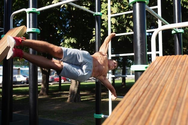 Спортсмен делает упражнения на стадионе в парке