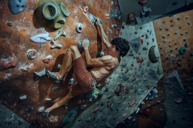 Свободный альпинист молодой человек восхождение на искусственный валун в помещении