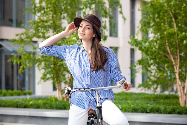 通りで自転車に乗って帽子でかわいい女の子