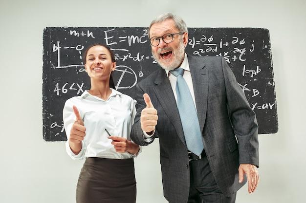 Мужской профессор и молодая женщина против доске в классе