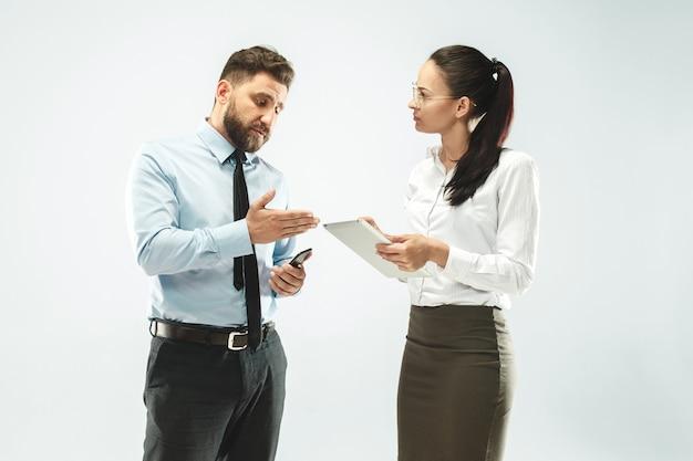 ビジネスマンはオフィスで彼の同僚にラップトップを示します。