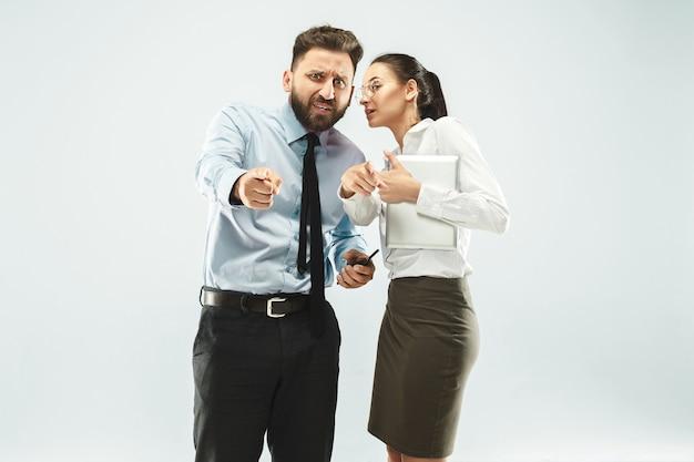 怒ったボス。男と彼の秘書がオフィスやスタジオに立っています。