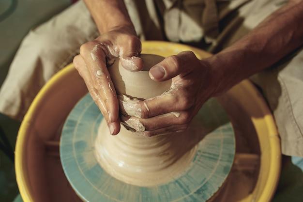Создание банки или вазы из белой глины крупным планом. мастер черепок.