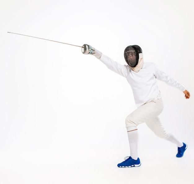Человек в фехтовальном костюме тренируется с мечом против серого