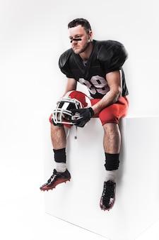 ヘルメットと座っているアメリカンフットボール選手