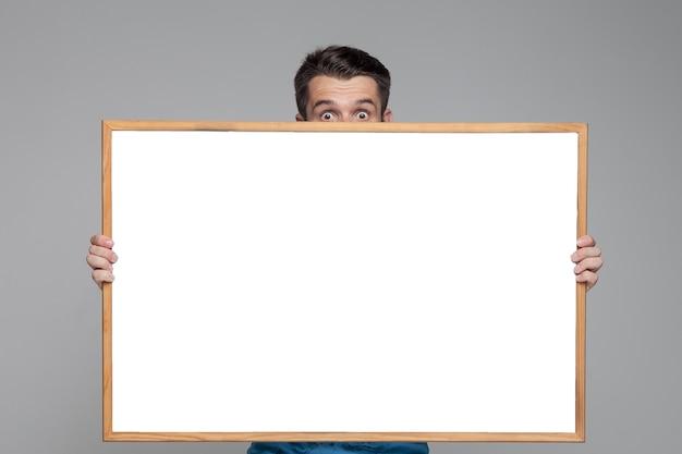 空のホワイトボードを示す驚いた男