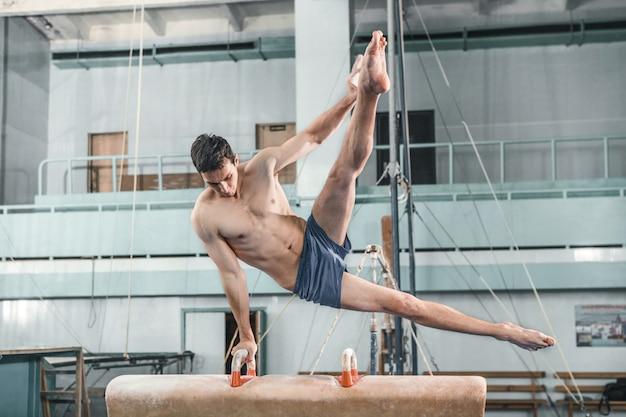 Спортсмен во время сложных упражнений, спортивная гимнастика