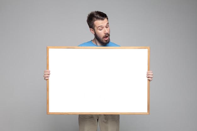 Удивленный человек показывая пустую белую доску
