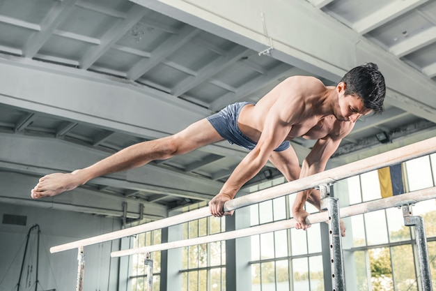 平行棒で逆立ちを行う男性の体操選手