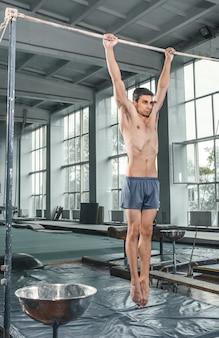 Мужской гимнаст выполняет стойку на руках на параллельных брусьях