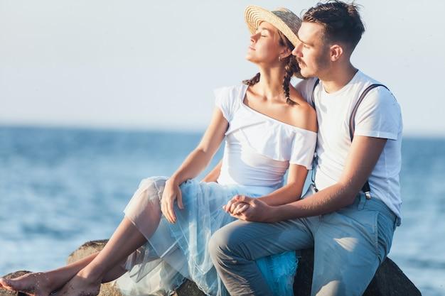 Счастливая молодая романтическая пара отдыхает на пляже и смотрит на закат