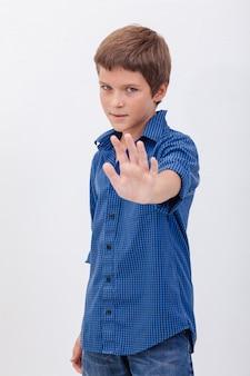 Красивый мальчик делает знак стоп