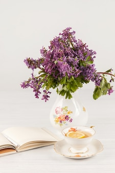 テーブルの上のライラックサクラソウの花束とレモンティー