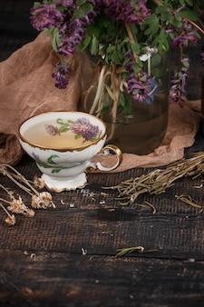 テーブルの上のサクラソウの花束とレモンティー