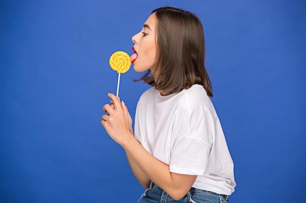 カラフルなロリポップを持つ若い女