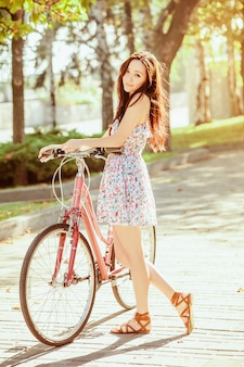 公園で自転車を持つ若い女性
