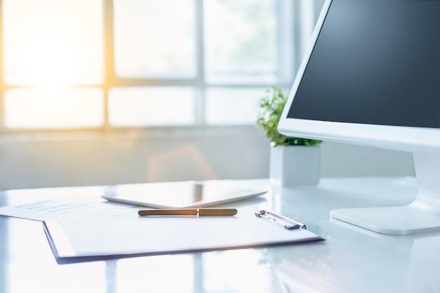 コンピューターとクリップボードのオフィスデスク