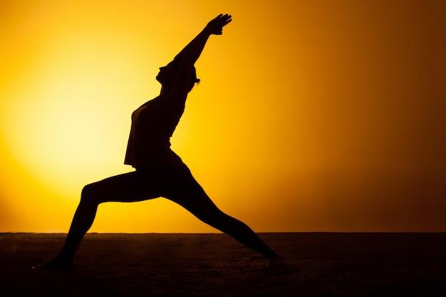 夕日の光の中でヨガの練習の女性