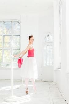 Балерина позирует в пуанты в белом деревянном павильоне