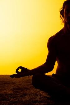 Человек практикующих йогу в лучах заката