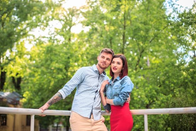 公園に立って、明るく晴れた日に笑って幸せな若いカップル