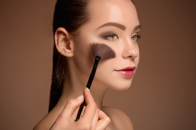 Молодая женщина, надевая макияж