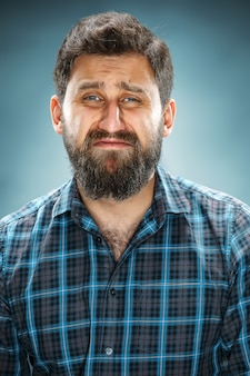 Плачущий человек в синей рубашке